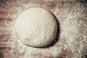 bread dough on wooden, floured surface