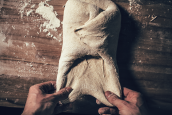 baker stretching out folded bread dough from bottom