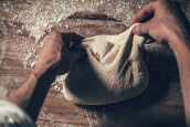 baker pinching ends of folded bread dough together